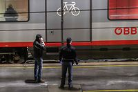 Picture taken on February 23, 2020 shows two policemen standing in front of a train of the �sterreichische Bundesbahnen (�BB) Austrian railway company on a platform of the railway station in Gries am Brenner at the Austrian-Italian border. - An Austrian train from Venice bound for Munich was stopped on Sunday, February 23, 2020, on the Italian side of the Brenner Pass border crossing with Austria because of two possible cases of coronavirus, the Austrian interior ministry said. It later announced that the passengers had tested negative and train services resumed. (Photo by Johann GRODER / APA / AFP) / Austria OUT