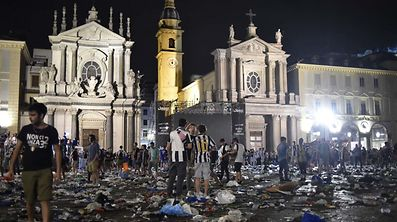 Juventus fan run away following panic created by the explosion of firecrackers as they watched the match on a giant screen