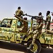 Sudanese soldiers flash the victory gesture as they sit in the back of a technical (pickup truck mounted with a turret) nearby a scene of gathering demonstrators during a rally demanding a civilian body to lead the transition to democracy, outside the army headquarters in the Sudanese capital Khartoum on April 13, 2019. - Sudan's new military leader General Awad Ibn Ouf resigned late on April 12 just a day after being sworn in, as the country's army rulers insisted they would pave the way for a civilian government. (Photo by AHMED MUSTAFA / AFP)