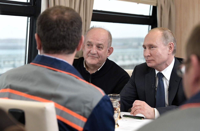 Der russiche PRäsident spricht mit Arbeitern in einem Abteil des neuen Zuges.