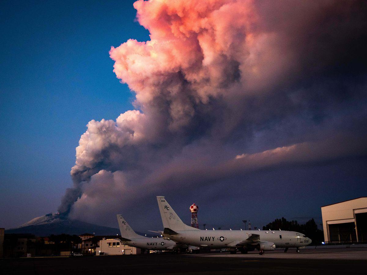 Catania: Flugzeuge stehen auf der US Naval Basis Sigonella, während im Hintergrund Rauschschwaden aus dem Vulkan Ätna aufsteigen.