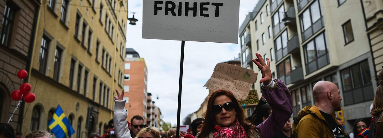 """A woman holds a sign with the reading """"freedom"""" as she attends a march through the streets of Stockholm to a public park to protest against the country's Covid-19 restrictions, on May 1, 2021. (Photo by Jonathan NACKSTRAND / AFP)"""