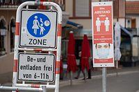 25.03.2021, Saarland, Mettlach: Menschenleer ist die Fußgängerzone. Schilder weisen auf die Maskenpflicht und die 1,5-Meter-Abstandsregel hin. Nach Ostern sollen viele Betriebe, Geschäfte und Außengastronomien im Saarland wieder öffnen dürfen. Das Saarland will dann mit dem Ausstieg aus dem Lockdown beginnen. Foto: Harald Tittel/dpa +++ dpa-Bildfunk +++