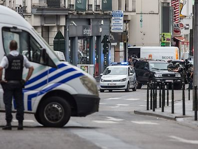 """A police officer stands behind a van during a police intervention in central Brussels on July 20, 2016, to surround a """"suspect"""" individual. Police backed by bomb disposal teams on July 20 cordoned off part of central Brussels where they surrounded a """"suspect"""" individual wearing a long coat with wires showing. """"Following police intervention, a cordon has been established"""" around part of the Place de la Monnaie and adjoining streets, Brussels police said in a tweeted message. / AFP PHOTO / Belga / SISKA GREMMELPREZ / Belgium OUT"""