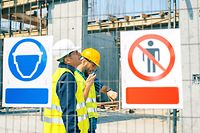 Engineer and construction site manager dealing with blueprints and projects. Construction site warning signs. Arbeitsunfall, Arbeitsunfälle, sicherheit am Arbeitsplatz, Baustelle, Helmpflicht
