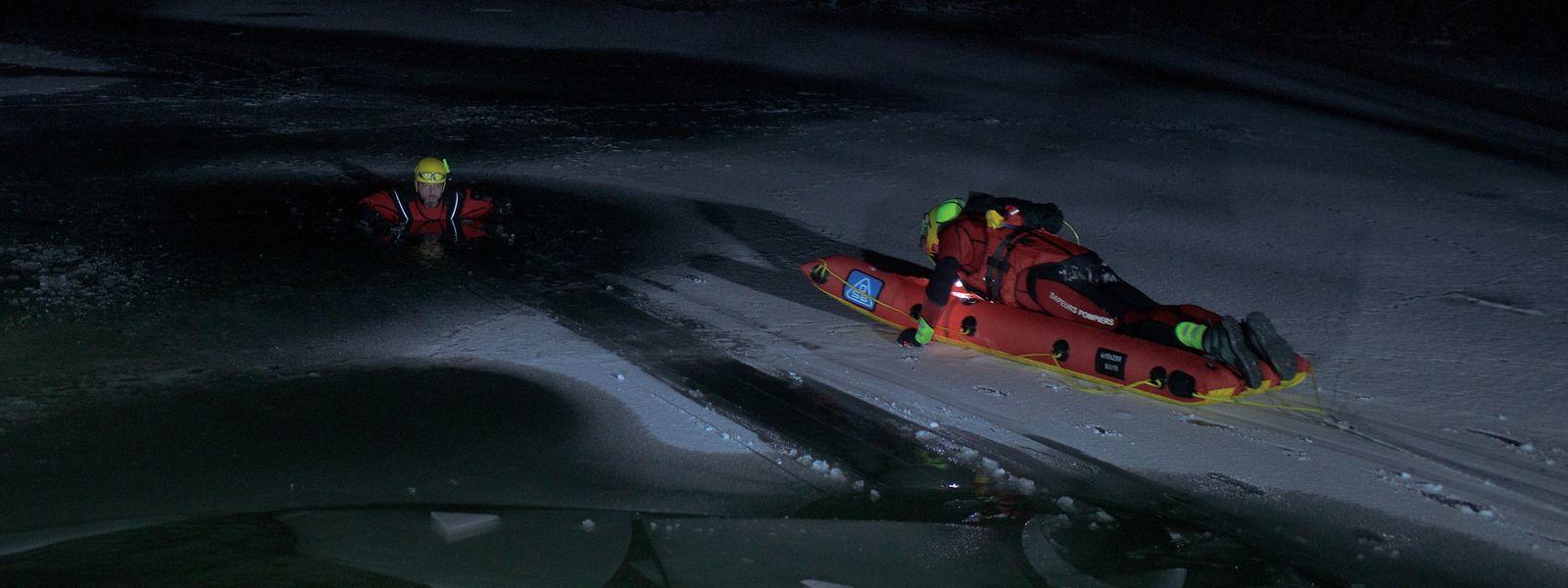 Mit Eispickeln aus Plastik bewegen sich die Retter auf dem Luftkissen vorwärts.