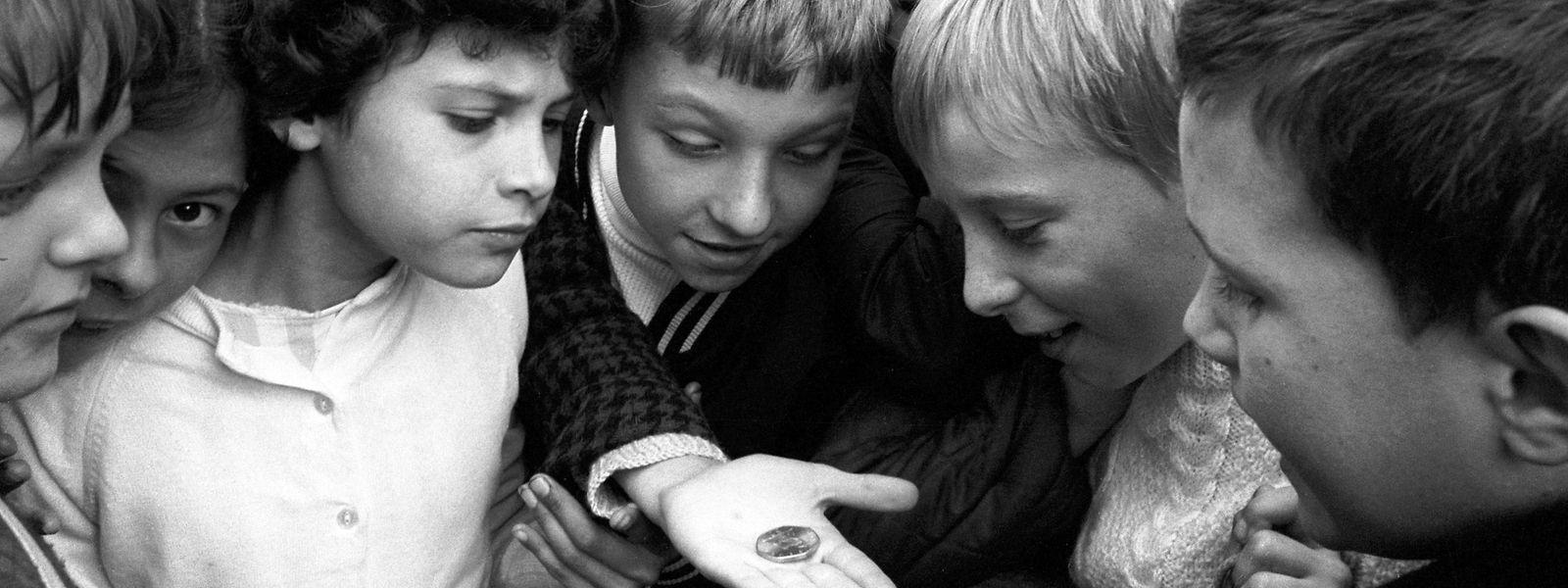 Kinder betrachten am Trafalgar Square in London die neue dezimale 50-Pence-Münze.