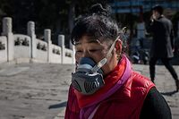A woman wearing a facemask as a preventive measure against the COVID-19 coronavirus walks on a bridge at the Summer Palace in Beijing on March 17, 2020. - China reported on March 17 just one new domestic coronavirus infection but found 20 more cases imported from abroad, with more regions imposing quarantines on foreign arrivals in a bid to stem the disease being brought in from overseas. (Photo by NICOLAS ASFOURI / AFP)