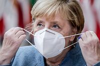 German Federal Chancellor Angela Merkel removes her face mask as she arrives ahead of a two days European Union (EU) summit at the European Council Building in Brussels, on October 15, 2020. - European leaders meet to re-examine the post-Brexit talks under pressure from English Prime Minister to give ground or see Britain walk away with no trade deal. (Photo by Olivier HOSLET / POOL / AFP)