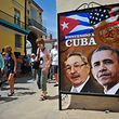 Tourists walk next to a poster of Cuban President Raul Castro and US president Barack Obama in Havana, on March 18, 2016. US president Barack Obama touches down in Havana on Sunday to cap a long-unimaginable rapprochement with Cuba and burnish a presidential legacy dulled by Middle East quagmires and partisan sniping. As Air Force One rolls to a stop, Obama will become the first sitting US president to visit Cuba since Calvin Coolidge arrived on a battleship in 1928, before the discovery of penicillin or invention of the ballpoint pen.      AFP PHOTO/YAMIL LAGE