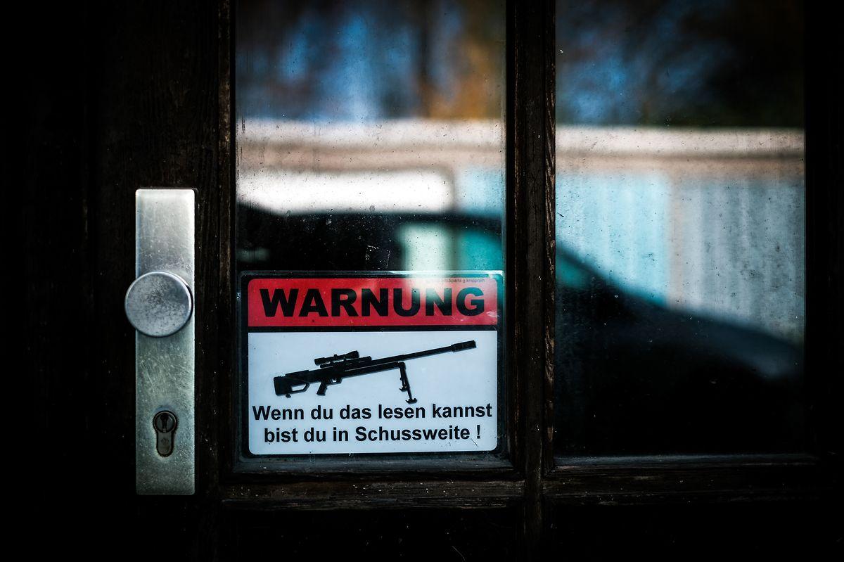 """Se consegues ler este anúncio estás ao alcance da arma"", na porta de um edifício abandonado na antiga Alemanha de Leste."