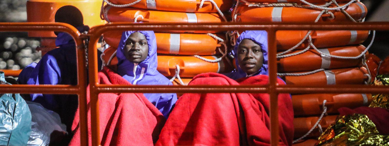 Migranten sitzen in Decken gehüllt im Hafen von Malaga.