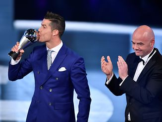 Real Madrid and Portugal's forward Cristiano Ronaldo (L) kisses his trophy after winning the The Best FIFA Men�s Player of 2016 Award next to FIFA president Gianni Infantino during The Best FIFA Football Awards ceremony, on January 9, 2017 in Zurich. / AFP PHOTO / Fabrice COFFRINI