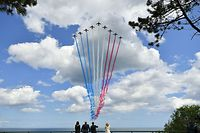 """(From L) US First Lady Melania Trump, US President Donald Trump, French President Emmanuel Macron and French President's wife Brigitte Macron watch as French elite acrobatic flying team """"Patrouille de France"""" (PAF) fly over after a French-US ceremony at the Normandy American Cemetery and Memorial in Colleville-sur-Mer, Normandy, northwestern France, on June 6, 2019, as part of D-Day commemorations marking the 75th anniversary of the World War II Allied landings in Normandy. (Photo by MANDEL NGAN / AFP)"""