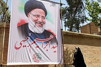 AN Iranian woman walks past an electoral poster depicting judiciary chief and presidential candidate Ebrahim Raisi in the capital Tehran, on May 29, 2021. - Iran's presidential election campaign officially kicked off yesterday, without fanfare and in an atmosphere of indifference as many say the result is a foregone conclusion. (Photo by ATTA KENARE / AFP)