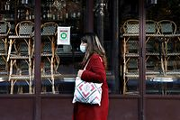 (FILES) In this file photo taken on November 18, 2020 a woman walks past a closed restaurant in Paris amid a second lockdown in France aimed at containing the spread of Covid-19 pandemic caused by the novel coronavirus. (Photo by THOMAS COEX / AFP)