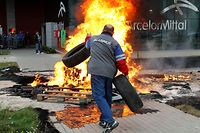 An ArcelorMittal steel worker throws tyres into a fire during a strike outside the company's regional headquarters in Flemalle, near Liege October 4, 2011. Union members have prevented the management of ArcelorMittal site at Flemalle from leaving the building since Monday evening, local media reported. The unions are demanding the management to come to an agreement about the payment for temporary contract workers and are protesting against rumours of ArcelorMittal shutting down factories. REUTERS/Thierry Roge (BELGIUM - Tags: BUSINESS EMPLOYMENT CIVIL UNREST TPX IMAGES OF THE DAY)