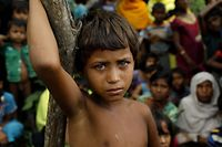 TOPSHOT - A Rohingya refugee girl looks next to newly arrived refugees who fled to Bangladesh from Myanmar in Ukhiya on September 6, 2017.   More than 125,000 refugees have flooded across the border into Bangladesh. Most are Rohingya, a Muslim ethnic minority that the government of Buddhist-majority Myanmar largely does not recognise as citizens.  / AFP PHOTO / K M ASAD
