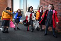 Pupils arrive at Clyde Primary School in Glasgow on February 22, 2021 as schools in Scotland started to reopen to more of the youngest students in an easing of the coronavirus shutdown. (Photo by Andy Buchanan / AFP)