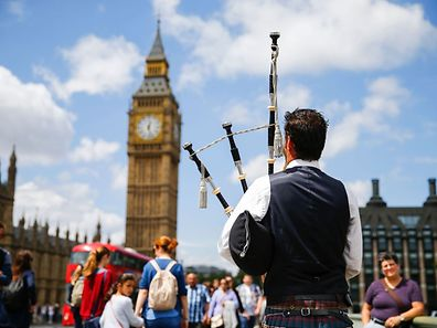 A Scottish piper plays for tourists in front of the Queen Elizabeth Tower (Big Ben)