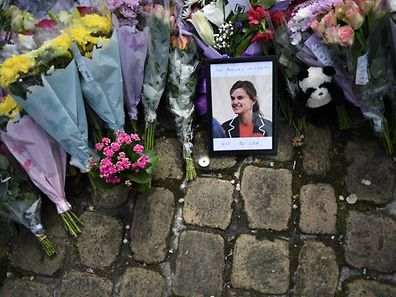 "A photograph of slain Labour MP Jo Cox sits amongst flowers left in tribute to her in Birstall, northern England, on June 18, 2016, following her murder on June 16. British lawmaker Jo Cox's alleged killer Thomas Mair ranted against ""traitors"" during a brief court appearance in London on Saturday, as EU referendum campaigning was suspended for a third day in tribute to the slain MP. / AFP PHOTO / OLI SCARFF"