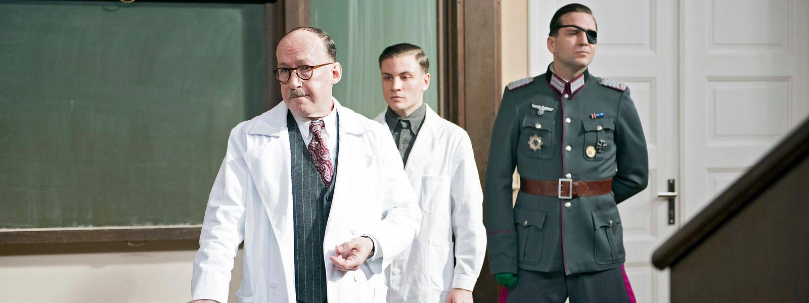 Prof. Sauerbruch (Ulrich Noethen, l.), Otto Marquardt (Jannik Schümann, M.) und Claus Schenk Graf von Stauffenberg (Pierre Kiwitt, r.) im Hörsaal der Charité.