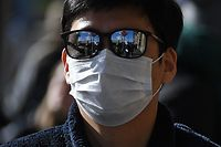 A London Underground sign is reflected in the sunglasses of a tourist, wearing surgical face mask in central London on March 2, 2020. - Britain's Prime Minister Prime Minister on Monday chaired an emergency COBRA meeting on the coronavirus outbreak, after the number of confirmed cases of COVID-19 in the United Kingdom rose to 36. (Photo by DANIEL LEAL-OLIVAS / AFP)