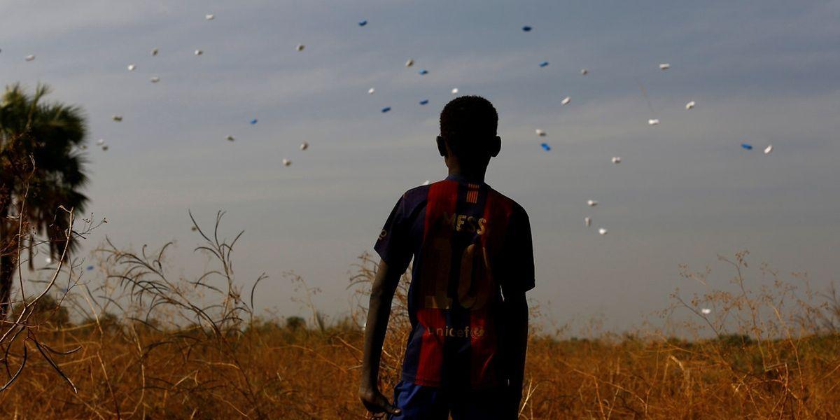 Eine Junge sieht zu, wie ein Flugzeug des UN-Welternährungsprogramms Beutel mit Lebensmitteln über dem Südsudan abwirft.