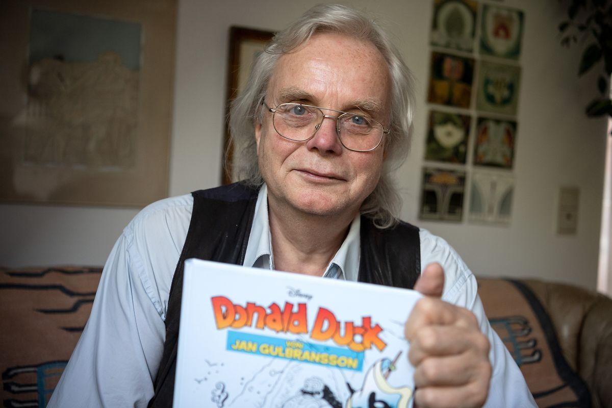 Jan Gulbransson sitzt mit einem Sammelband seiner Comics in seiner Wohnung in München.
