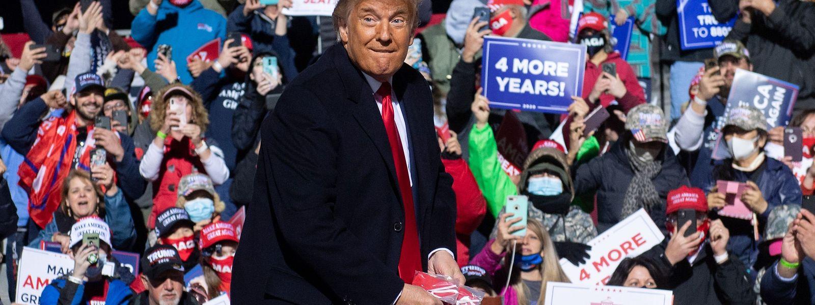 Donald Trump - ohne Maske - verteilt Masken an seine jubelnden Anhänger bei einer Wahlkampfveranstaltung.