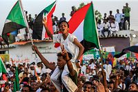 "A Sudanese boy wearing facepaint on his forehead reading in Arabic ""civilian"" chants slogans while seated on the shoulders of a man as people celebrate after protest leaders struck a deal with the ruling generals on a new governing body, in the capital Khartoum's eastern district of Burri on July 5, 2019, - The deal, reached in the early hours of July 5 after two days of hard-won talks brokered by Ethiopian and African Union mediators, provides for the interim governing body to have a rotating presidency, as a compromise between the positions of the generals and the protesters. The blueprint proposes that a general hold the presidency for the first 18 months of a three-year transition, with a civilian taking over for the rest. (Photo by ASHRAF SHAZLY / AFP)"