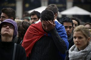 A man wrapped in the French flag reacts as people gather to pay tribute to the victims of a series of coordinated attacks in and around Paris, in Toulouse on November 14, 2015. At least 128 people were killed in the Paris attacks on the evening of November 13, with 180 people injured, 80 of them seriously, police sources told AFP.   AFP PHOTO / PASCAL PAVANI