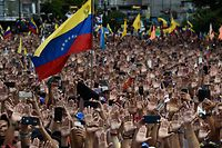 """- AFP PICTURES OF THE YEAR 2019 -   People raise their hands during a mass opposition rally against President Nicolas Maduro in which Venezuela's National Assembly head Juan Guaido (out of frame) declared himself the country's """"acting president"""", on the anniversary of a 1958 uprising that overthrew a military dictatorship, in Caracas on January 23, 2019. - """"I swear to formally assume the national executive powers as acting president of Venezuela to end the usurpation, (install) a transitional government and hold free elections,"""" said Guaido as thousands of supporters cheered. Moments earlier, the loyalist-dominated Supreme Court ordered a criminal investigation of the opposition-controlled legislature. (Photo by Federico PARRA / AFP)"""