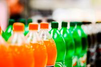 A long line of unbranded soda bottles in various flavours and colors, the focus on the center of the line. Soft drinks Zucker Plastik Plastique Flaschen Bouteille