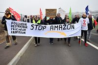(FILES) In this file photograph taken on January 24, 2020, protesters hold banners and placards during a demonstration against the installation of a warehouse of the online retailer Amazon on the former military air base of Frescaty, at Augny, north-eastern France. - From Metz to Belfort, giant warehouse projects are multiplying in the north-east of France, in the heart of Western Europe, but their opponents are brandishing the name Amazon like a scarecrow and are betting on the recent green wave to stand in their way. 185,000 m2 on a former airbase near Metz, 76,000 m2 on another near Belfort, 150,000 m2 in Dambach-la-Ville (Bas-Rhin), 190,000 m2 in Ensisheim (Haut-Rhin): while logistics platform projects are flourishing throughout France, those in the north-eastern quarter are particularly dizzying. (Photo by JEAN-CHRISTOPHE VERHAEGEN / AFP)