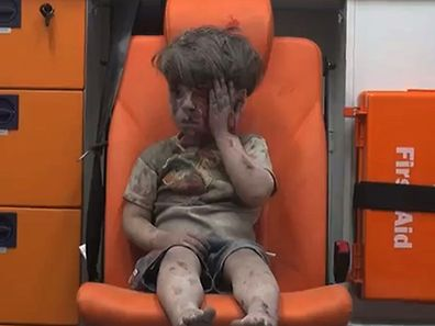 """An image grab taken from a video uploaded by the Syrian opposition's activist group Aleppo Media Centre (AMC) on August 17, 2016 is said to show a young Syrian boy covered in dust and blood touching a wound on his head as he sits in shock in an ambulance after being rescued from the rubble of a building hit by an air strike in the rebel-held Qaterji neighbourhood of the northern Syrian city of Aleppo. / AFP PHOTO / AMC / HO / === RESTRICTED TO EDITORIAL USE - MANDATORY CREDIT """"AFP PHOTO / HO / AMC """" - NO MARKETING NO ADVERTISING CAMPAIGNS - DISTRIBUTED AS A SERVICE TO CLIENTS FROM ALTERNATIVE SOURCES, AFP IS NOT RESPONSIBLE FOR ANY DIGITAL ALTERATIONS TO THE PICTURE'S EDITORIAL CONTENT, DATE AND LOCATION WHICH CANNOT BE INDEPENDENTLY VERIFIED ===   /"""