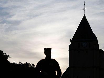 Un policier se tient à proximité de l'église Saint-Etienne à Saint-Etienne du Rouvray au lendemain du meurtre sordide du prêtre Jacques Hamel dans son église par deux jeunes se réclamant de l'organisation terroriste Etat islamique.