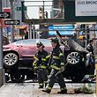 NEW YORK, NY - MAY 18: Firefighters walk past a wrecked car in the intersection of 45th and Broadway in Times Square, May 18, 2017 in New York City. According to reports there were multiple injuries and one fatality after the car plowed into a crowd of people.   Drew Angerer/Getty Images/AFP