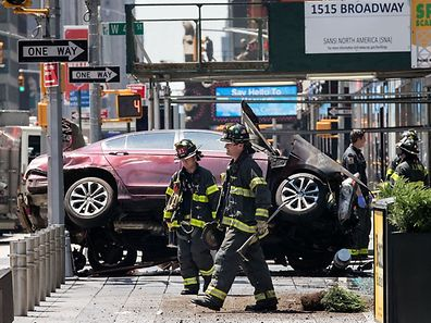 NEW YORK, NY - MAY 18: Firefighters walk past a wrecked car in the intersection of 45th and Broadway in Times Square, May 18, 2017 in New York City. According to reports there were multiple injuries and one fatality after the car plowed into a crowd of people.   Drew Angerer/Getty Images/AFP == FOR NEWSPAPERS, INTERNET, TELCOS & TELEVISION USE ONLY ==