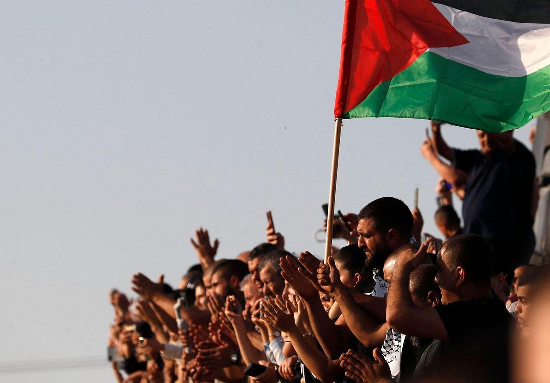 Os enlutados levantam uma bandeira palestiniana durante o funeral de Mohammad Kiwan, um palestiniano de 17 anos que sucumbiu às suas feridas depois de ter sido baleado pelas tropas israelitas durante os protestos contra a ocupação israelita. (Photo by Ahmad GHARABLI / AFP)