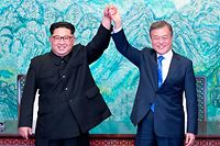 "TOPSHOT - North Korea's leader Kim Jong Un (L) and South Korea's President Moon Jae-in (R) raise their jointed hands during a signing ceremony near the end of their historic summit at the truce village of Panmunjom on April 27, 2018. The leaders of South and North Korea embraced warmly after signing a statement in which they declared ""there will be no more war on the Korean Peninsula"". / AFP PHOTO / Korea Summit Press Pool / Korea Summit Press Pool"
