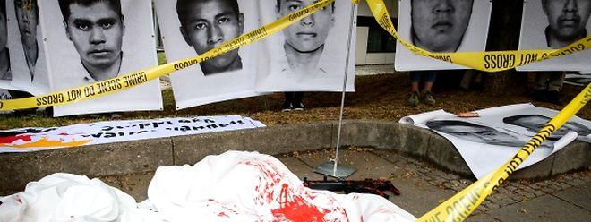 """Mit Fotos und Waffenattrappen machen Waffengegner auf die 43 Studenten aufmerksam, die 2014 in Mexiko entführt und mutmaßlich ermordet wurden. Laut der Organisation """"Deutsche Menschenrechtskoordination Mexiko"""" wurden bei dem Vorfall Waffen von Heckler & Koch eingesetzt."""