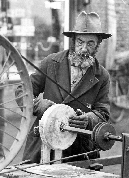 Een scharensliep aan het werk. Hij houdt de slijpsteen vast, die door een fietswiel dmv een snaar wordt aangedreven. [1931].