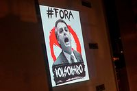 "TOPSHOT - View of a projection depicting Brazil's President Jair Bolsonaro which reads ""Bolsonaro Out"" as part of daily protests called ""Panelacos"", during the outbreak of the novel coronavirus COVID-19 in Rio de Janeiro, Brazil, on March 26, 2020. (Photo by Mauro PIMENTEL / AFP)"