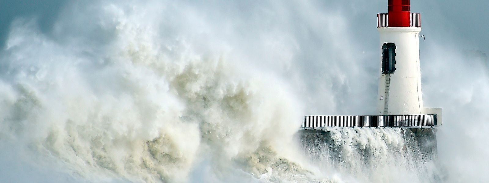 (FILES) This file photo taken on February 9, 2016 shows waves breaking against a pier and a lighthouse in Les Sables-d'Olonne, western France. Deaths due to weather-related disasters in Europe could increase fifty-fold from an estimated 3,000 per year recently to 152,000 by century's end, mainly due to climate change, researchers warned on August 5, 2017.  / AFP PHOTO / LOIC VENANCE