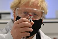 Britain's Prime Minister Boris Johnson poses for a photograph with a vial of the AstraZeneca/Oxford University COVID-19 candidate vaccine, known as AZD1222, at Wockhardt's pharmaceutical manufacturing facility in Wrexham, north Wales, on November 30, 2020. - Britain's Government in August announced a deal with global pharmaceutical and biotechnology company Wockhardt, to increase capacity in a crucial part of the manufacturing process for Covid-19 vaccines. Britain has been Europe's worst-hit country during the pandemic, recording more than 57,000 deaths from some 1.6 million cases. (Photo by Paul ELLIS / POOL / AFP)
