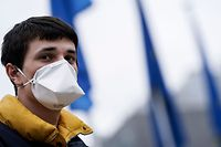 "A man wearing a face mask as a preventive measure looks on in front of the EU headquarters in Brussels on March 16, 2020. - After more than a year without a full government, Belgium's bickering parties have agreed to back caretaker prime minister Sophie Wilmes and give her ""special powers"" to fight the coronavirus. Wilmer's government has ordered a partial lockdown, with schools, bars and restaurants closed, large gatherings cancelled and employees who can do so advised to work from home. (Photo by Kenzo TRIBOUILLARD / AFP)"