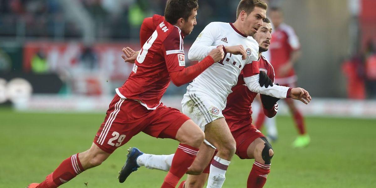 Bayern Münchens scheidender Verteidiger Philipp Lahm setzt sich gegen zwei Ingolstädter durch.