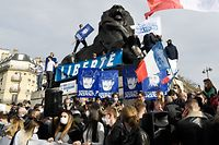 """Members and supporters of far right group Generation Identitaire (GI) deploy a banner reading """"Freedom"""" on the Lion de Belfort sculpture during a protest against its potential dissolution in Paris on February 20, 2021. - The dissolution of Generation identitaire was evoked for the first time on January 26, 2021 by Interior Minister, as a reaction to the group's recent anti-migrant operation in the Pyrenees, which led to a preliminary investigation for provocation to racial hatred. (Photo by Bertrand GUAY / AFP)"""