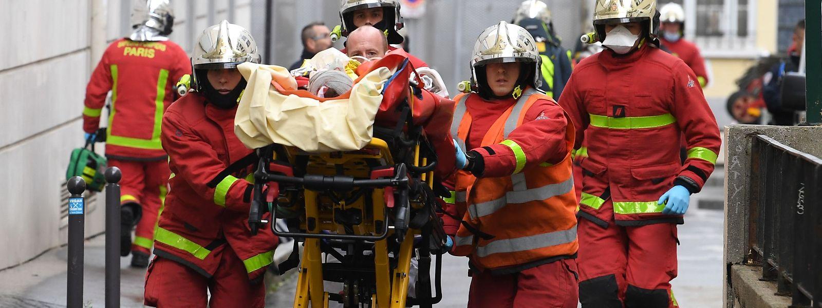 Einsatzkräfte der Feuerwehr schieben eine Trage mit einem Verletzten.